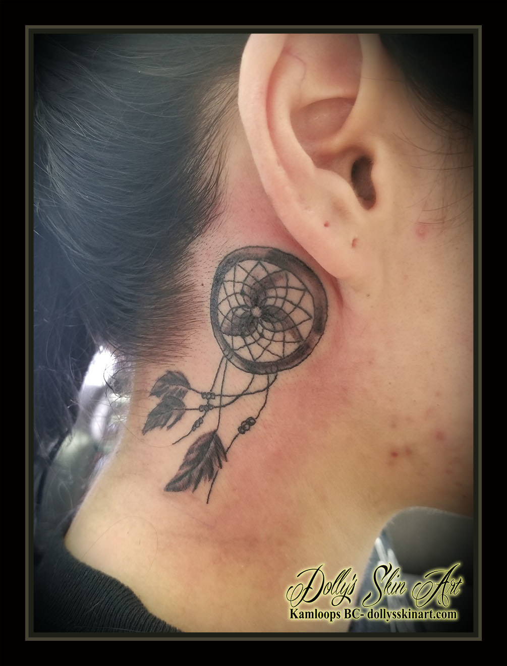 black and grey dreamcatcher behind ear feathers shaded small simple tattoo kamloops dolly's skin art