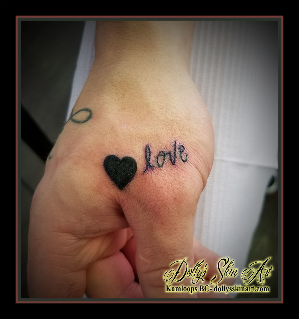 small simple solid black heart love lettering font script hand thumb tattoo kamloops dolly's skin art